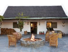 Country house with fire pit and Spanish / Texas Ranch flair - White stucco building exterior