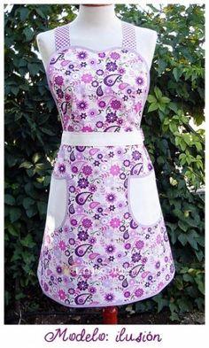 Delantal hecho de forma artesanal con un diseño exclusivo de HJ Labores.  En estampado floral combinado coordinado con beige y vichy violeta. El pechero en forma de corazón le da un aire muy romántico.