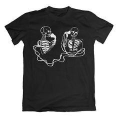 Vintage 1909 illustration of skeletons on an early telephone  white print on black t-shirt  100% combed and ring spun cotton.  Shirts take 3-5 business days to process before shipping.  Male model is a size small wearing a size small shirt  Please be sure to see below for sizing information!  Shirts are printed using direct to garment printing with eco friendly water based inks.  Measurements  XS body width: 16.5 body length: 27  S body width: 18 body length: 28  M body width: 20 body…