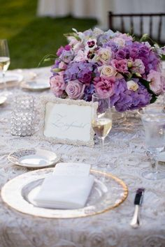 An ivory textured floral linen adds interest to a table top design. Gold rimmed chargers and purple blush roses are beyond elegant in the California Wine Country. Ditch table numbers and use creative table names for any wedding.