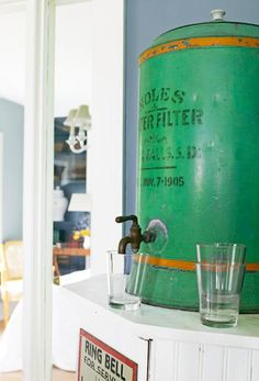 """House Tour: Decorate with Vintage Finds   Midwest Living. She has this vintage water filter in the dining room to dispense a drink with a """"ring for service"""" vintage sign under it."""