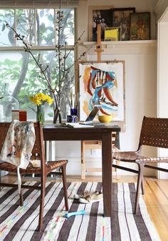 A shelf full of paintings adds personality to a dining room.