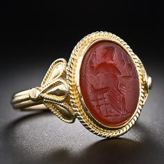 A lovingly-worn amber color carnelian bears what is apparently an very old carving of a a Greek or Roman mythological subject presented in a 22 karat ring, hand crafted to emulate an ancient counterpart. Unique.
