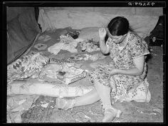 Woman quilting in her tent during the Great Depression.