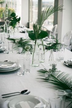 Simple, modern, elegant. White linens and china with tropical greenery in glass bottles, perfect for a Florida wedding.