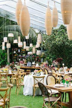 Casamento na Praia do Forte com decoração rústica sofisticada e elegante. Mesa de doces com composição de móveis, com luminárias de palha e vasos coloridos.      Foto: Duo Borgatto.