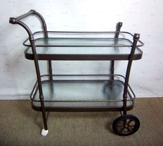 Rustic Serving Cart, Bronze Color, 2 Glass Shelves, 4 Wheels - Warner Bros. Property Department