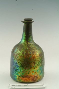 English early 1700s  Wine bottle, natural green glass, very iridescent and exfoliating; cylindrical body; neck with applied (irregular) collar below rim; rounded basal edge; wide domed kick with unpolished pontil mark.
