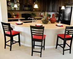 L-shaped kitchen with dark and white cabinetry.  Large pie-shaped island forms the center of the kitchen and includes extensive eat-in area on the outside facing the kitchen