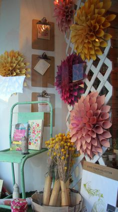 Paper dahlias in our garden inspired window display at Poppins, Mackinac Island. Salon Window Display, Boutique Window Displays, Spring Window Display, Window Display Design, Store Window Displays, Autumn Window Display Retail, Retail Displays, Merchandising Displays, Paper Dahlia