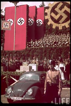 """LIFE Magazine's coverage of the 1938 presentation of the """"Kraft durch Freude"""" (""""Strength through Joy"""") Wagen, or KdF-Wagen, the readily-recognizable ancestor of the postwar Volkswagen """"Beetle"""". The Strength through Joy program was a Nazi leisure organization operated by the German Labor Front, the logo of which is the swastika-in-gear insignia visible in the picture. Adolf Hitler is also visible at the podium."""