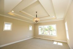 A gorgeous master bedroom! This bedroom with large windows, transom windows, and a double-box tray ceiling makes this room feel bright and open. Our craftsmanship is shown again here in this bedroom with oversized baseboards, jammed and cased windows, and crown molding!