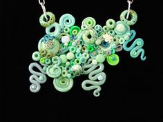 This necklace is made out of polymer clay and features a re-purposed chain.