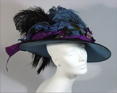 Circa 1900 hat (side view) | Label: The Bonita Hat | Huge oblong circle shape made of black plush with flamboyant turquoise lining that shows. It is trimmed with black and turquoise ostrich plumes. There is a turquoise and purple ribbon and velour 'grapes' on the ribbon