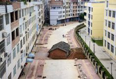 "A ""nail house,"" the last building in the area, sits in the middle of a road under construction in Nanning, Guangxi Zhuang Autonomous Region, China, on April 10, 2015. According to local media, the owner of the house didn't reach an agreement with the local authority about compensation of the demolition."