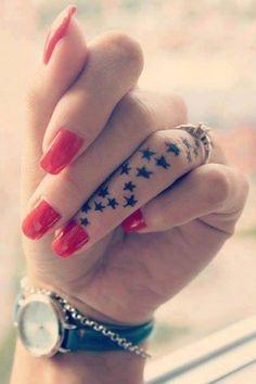 Pequeño tatuaje de dieciséis estrellas en el dedo anular.