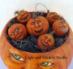 I recently completed a fun sculpture of a Mama Jack o' Lantern and her babies (pumpkin seeds). They are sculpted from paper clay over gourds.