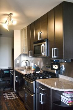 my kitchen, pink tiles under the cabinets, white counter, black cabinets silver (painted) appliances