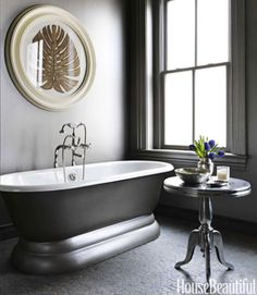 Bringing modern elegance to a Victorian row house in Washington, designer Barry Dixon creatively arranged furniture, painted ceilings, and connected rooms by weaving brown and white throughout. In the bathroom—walls, trim, ceiling, even the exterior of the Sunrise Specialty tub—has a silvery glow, thanks to Ralph Lauren's Regent Metallic Paint in Ambassador Sterling. Aluminum Wine table from Four Hands. Solistone Green Gobos pebble floor.