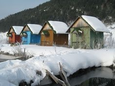 Four fishing shacks, each painted a different color, sit covered in snow beside a Siberian waterway