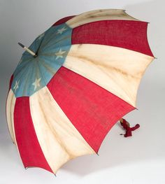 AMERICAN FLAG PARASOL, red, white, and blue fabric with six stars around top, original wooden handle. Circa 1876-1900.
