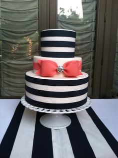 Wedding Cake -three circle tiers -top and bottom tier have white icing with 3 navy icing horizontal stripes -middle tier has white icing with a coral icing ribbon and bow with a crystal center in to bow