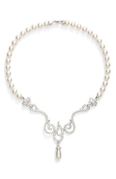 a20a7bfc6 A luminous faux-pearl necklace gets an elegant update from the swirling,  Swarovski crystal