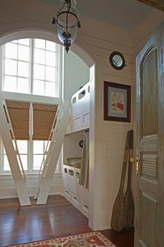 Bunk room with double height ceilings, a wall of windows, & old fashioned boat style bunks & ladders.      From House of Turquoise: Geoff Chick & Associates; in Watercolor,  Florida, and it's as pretty as that sounds - look at the whole house.
