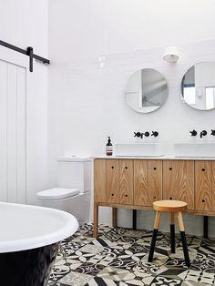 patterned floor tile + floating wood vanity + matte black faucets + white  brick tile + circle mirrors + barn door