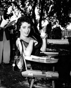 Elizabeth Taylor drinks a glass of milk on the MGM set of The Girl Who Had Everything. Portrait by Virgil Apger, 1953.