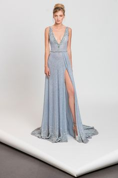 Fully embroidered light blue evening gown with deep V neckline in lace and silvery appliques.