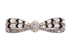 Länge: ca. 5,5 cm. Gewicht: ca. 12,5 g. Platin. Um 1920. Feine Art déco-Brosche in Schleifenform mit Diamanten im Alt- und Kissenschliff, zus. ca. 6,5 ct, und...