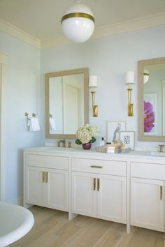 Angie Hranowski - Chic master bathroom design with blue walls paired with cream crown molding and bleached wood wood floors.