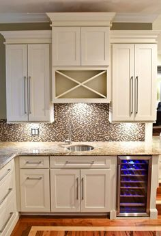 wet bar built of white shaker cabinets with built-in wine cooler in base and wine rack above sink