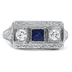 The Alida Ring from Brilliant Earth circa 1920's This distinctive three gem ring features a rich blue sapphire at the center and two round diamonds on either side, each set within square milgrain-bordered frames. The ring's amazing composition of endlessly detailed elements within a bold architectural setting is truly reminiscent of Art Deco glamour. (approx. 0.20 total carat weight).