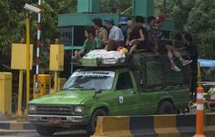 In this June 14, 2013 photo, passengers, including a Buddhist monk, travel atop a public transport passing a toll-gate in the outskirts of Yangon, Myanmar. (AP Photo/Gemunu Amarasinghe) ▼10Apr2014AP|Myanmar clunkers scrapped in rush for 'new' cars http://bigstory.ap.org/article/myanmar-clunkers-scrapped-rush-new-cars