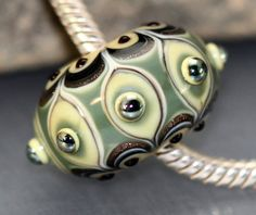 eautiful focal bead featuring a soft olive done in an intricate design with goldstone and reflective metallic accents.