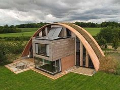 "Exterior: Windows facing south.  Green roof for insulation, solar panels to collect energy (technology). The ""Eco Arch"" home (Kent, England) eco design."
