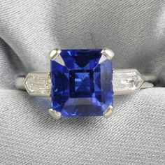 Art Deco Platinum, Sapphire, and Diamond Ring, prong-set with a rectangular emerald-cut sapphire measuring approx. 8.32 x 7.60 x 6.32 mm, and weighing approx. 3.95 cts., flanked by diamond bullets, no. 5027B, size 4 1/2, within a Cartier box.