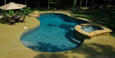 Located in Matthews, NC, this rustic free form pool features a jump rock and spa detailed in Tennessee crab orchard stone.