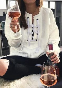 Model wears white ribbed lace-up sweatshirt with black ripped jeans