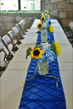 Reception tables at my wedding. Easy to do white linens with a blue runner. Take a mason jar ad fill with clear marbles add blue food dye in the water. The flowers are sunflowers baby breath and hydrangea.