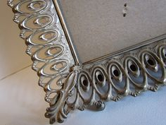 This oversized picture frame/vanity tray is perfect for the bedroom or bath, filled with antique perfume bottles, jewelry or knick knacks or a vintage photo. Would need a mirror to turn into a vanity tray or use wallpaper, fabric or scrapbooking paper under the glass. Has an Art Nouveau oval patterned border in gold metal with an oxidized white in the grooves. Decorative accents in the corners. Outer measurement is 15.5 x 12.75. Inside measurement is 13.5 x 10.25. Will fit an 11 x 14 pho...