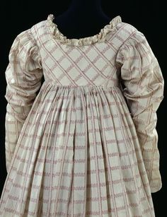 c. 1814. Thorny stems and leafy bands intersect on this dress, producing a trellis-like effect. They give the cotton a light and delicate appearance, which is heightened by the double neck frill and gathered sleeves. Similar garments are depicted in fashion plates of the time and in portraits by artists, particularly in the works of Jean-Auguste-Dominique Ingres (1780-1867).