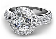 Four claw set round brilliant cut diamond engagement ring with pavé set diamonds in a halo design surround and rounded band.