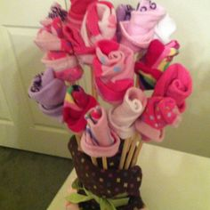 Baby socks into roses and a onesie as the base! I used chopsticks as the stems. Great way to give socks at a baby shower.
