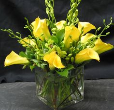 This is a cube vase floral arrangement that features yellow miniature calla lilies with accents of green dendrobium orchids.  See our entire selection at www.starflor.com.  To purchase any of our floral selections, as gifts or décor, please call us at 800.520.8999 or visit our e-commerce portal at www.Starbrightnyc.com. This composition of flowers is generally available for same day delivery in New York City (NYC). SQ125