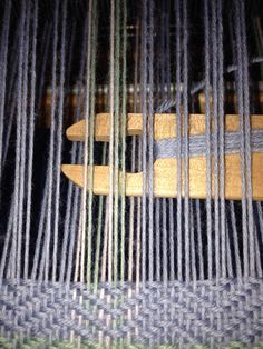 Shuttle in the shed while hand weaving fabric.