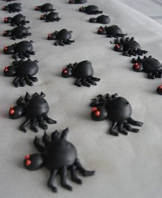 """Royal icing spiders for Oct.  Ice cake, """"smear"""" color on top, draw spider web, place spider on top of web.  Have kids make several spiders to take home"""