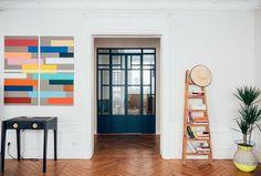 Ici, les tableaux hauts en couleurs d'Eva twistent la déco composée d'une table avec enceintes à gauche et d'une échelle en bois chinée, assortie d'un pot shoppé chez Gustave & Madeleine, à droite.